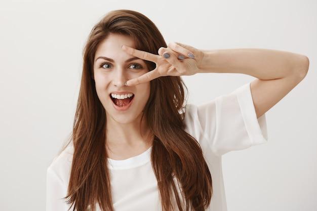 Donna sorridente allegra che mostra il segno di pace di kawaii sopra l'occhio