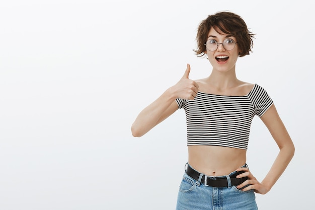 Cheerful smiling woman showing thumbs-up in approval, like and agree, recommend company service or product