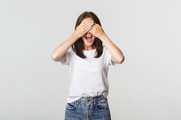 밝은 웃는 여자는 눈을 감고 놀라움을 기대합니다.