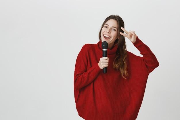 La donna sorridente allegra che canta in microfono, mostra il segno di pace