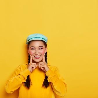 아시아 외모를 가진 쾌활한 웃는 여자, 검지 손가락으로 양 볼을 만지고, 미소가 결정되고, 핀업 메이크업을하고, 두 개의 땋은 머리가 있고, 캐주얼 한 옷을 입습니다.