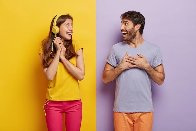 헤드폰으로 쾌활한 웃는 여자는 흥분하고 행복하게 느끼고 남자 친구를 바라보고 손을 쥐고