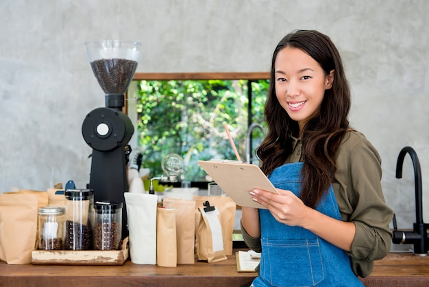 Cheerful smiling young asian woman entrepreneur at coffee shop counter