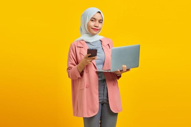 파란색 배경에 휴대전화와 노트북을 들고 쾌활하게 웃고 있는 젊은 아시아 여성