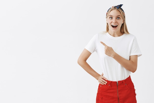 白い壁にポーズをとって陽気な笑顔の若いブロンドの女の子