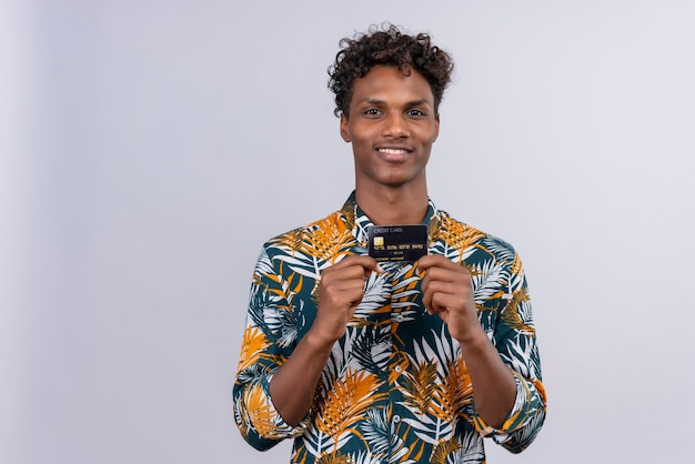 Cheerful and smiling young handsome dark-skinned man with curly hair in leaves printed shirt holding and showing credit card