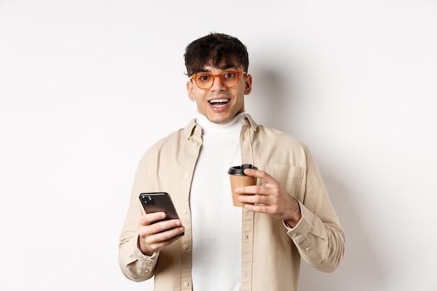 コーヒーを飲み、スマートフォンを持って、カメラに興奮して見て、白い背景の上に立っているメガネで陽気な笑顔の若い男。