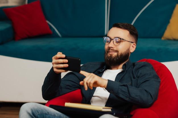 스마트 폰을 들고 안경에 밝은 웃는 젊은 남자와 재미있는 비디오를 시청하십시오.