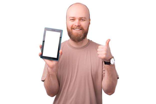 흰색에 태블릿 및 엄지 손가락에 빈 화면을 보여주는 수염과 밝은 웃는 젊은 남자