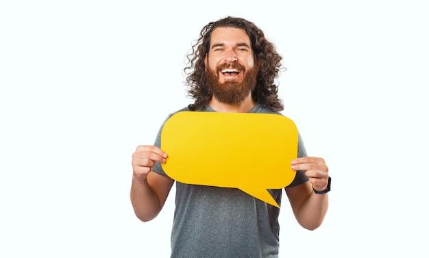 Веселый улыбающийся молодой студент, держащий пустой желтый речевой пузырь с copyspace