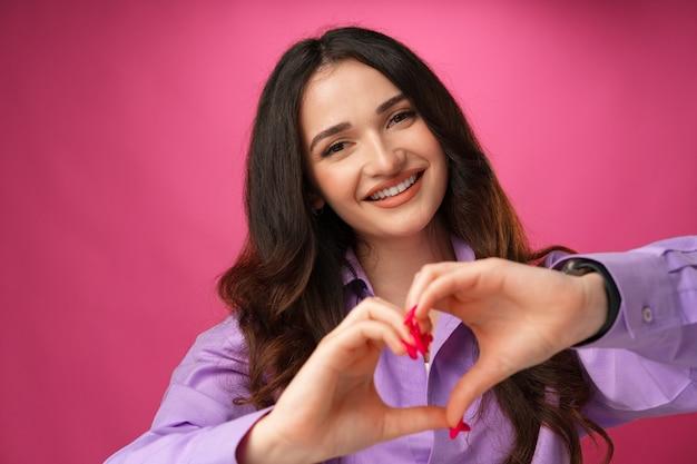 분홍색 배경에 심장 기호를 보여주는 쾌활한 웃는 젊은 여자