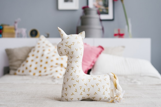 Cheerful soft unicorn toy on the bed