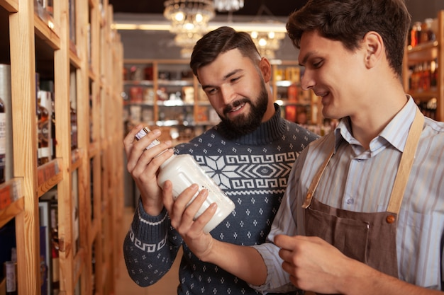 Cheerful sommelier helping his male customer choosing alcohol for the party. bearded man buying whiskey at the supermarket