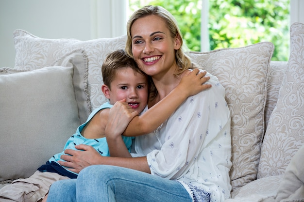 Cheerful son embracing mother on sofa
