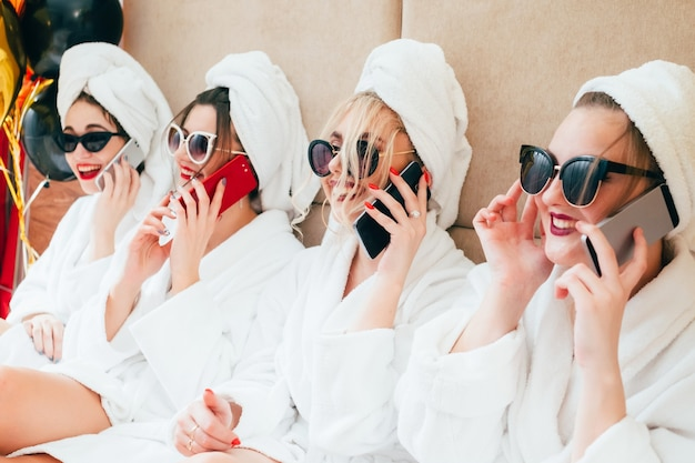 スマートフォンで話している陽気なスパの女の子。都会の女性のレジャーライフスタイル。サングラス、バスローブ、タオルターバン。