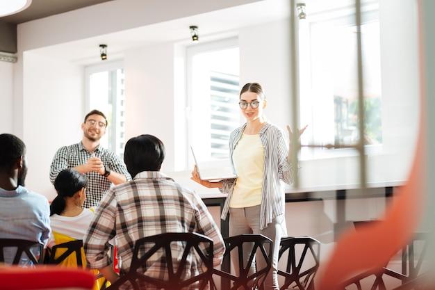 쾌활한 스피커. 영리한 경험이 풍부한 기업가가 유용한 비즈니스 워크숍을 진행하고 말하는 동안 청취자를 바라 봅니다.