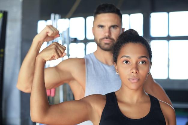 一緒にトレーニングし、ジムで上腕二頭筋を見せている陽気なスポーティーなカップル。