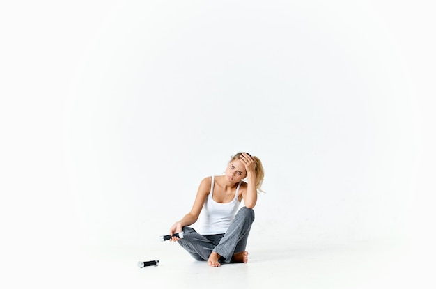 Cheerful sportive woman sitting on the floor dumbbells workout light background