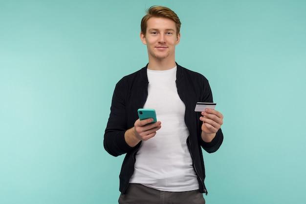 陽気なスポーツの赤毛の男がオンライン決済を行い、青い背景にスマートフォンを持っているカメラを見ます。 -画像