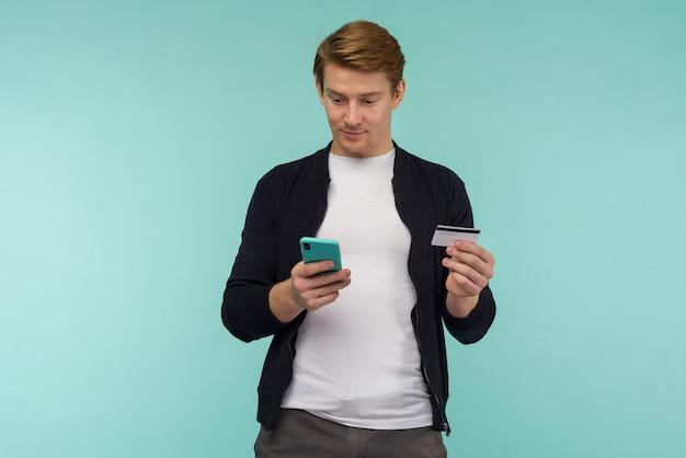 陽気なスポーツ赤毛の男がオンライン決済を行い、スマートフォンを見る