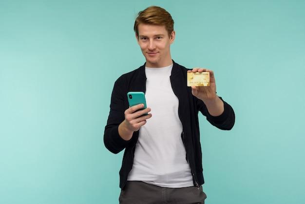 Веселый спортивный рыжеволосый парень проводит онлайн-платежи и показывает золотую кредитку