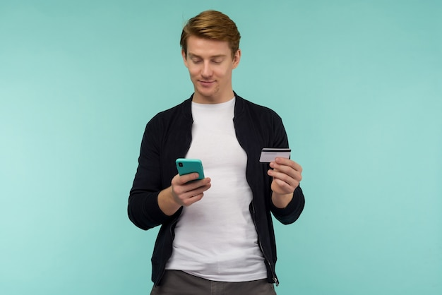 Cheerful sports red-haired guy conducts online payment and looks at the smartphone screen on a blue background. - image