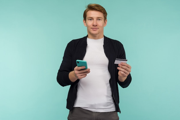 Cheerful sports red-haired guy conducts online payment and looks at the smartphone screen on a blue space.