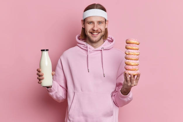 Cheerful sportsman holds bottle of milk and pile of doughnuts has temptation to eat junk food smiles happily