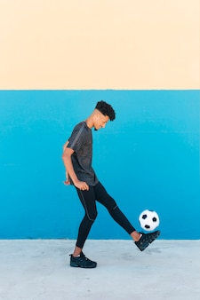 Cheerful sportsman kicking soccer ball near wall