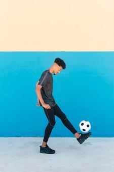 Cheerful sportsman kicking soccer ball near wall