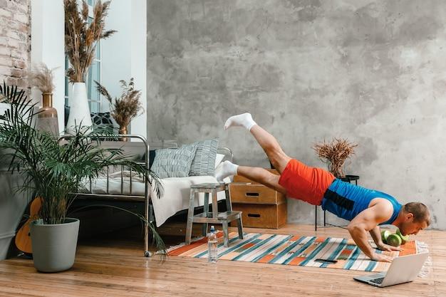 Веселый спортсмен с черными волосами делает отжимания и смотрит онлайн-тренировку с ноутбука в спальне