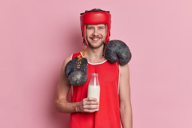 Lo sportivo allegro con i baffi e il sorriso felice sul viso indossa un cappello protettivo e porta i guantoni intorno al collo beve il latte dalla bottiglia di vetro per avere i muscoli che costruiscono il corpo e il carattere.