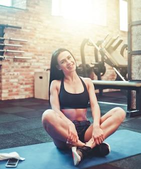 Веселая спортивная брюнетка женщина смотрит в камеру и улыбается, сидя на коврике в тренажерном зале