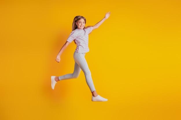Веселая спортивная девушка прыгает на желтом фоне