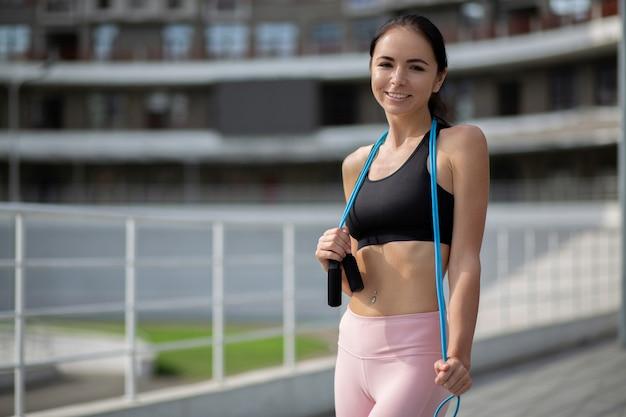 陽気なスポーティな女の子は、弾性抵抗バンドを保持しているスポーツアパレルを着ています。テキスト用のスペース