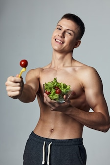 Cheerful sporty guy with pumped up abs plate salad healthy food cropped view
