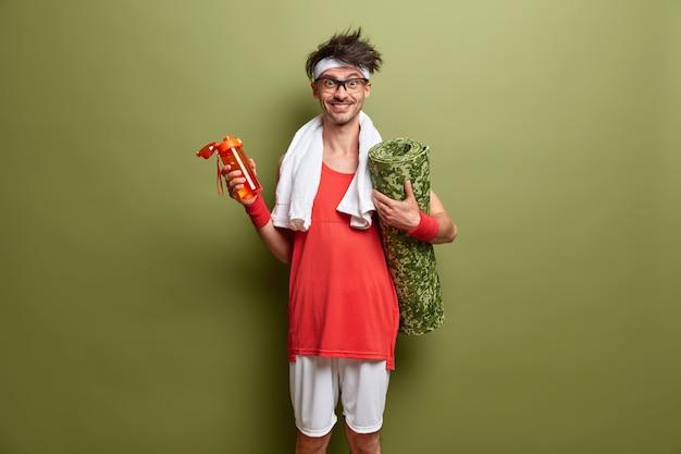 Karemat와 물 한 병을 가진 쾌활한 스포티 한 남자는 신체 운동을 할 예정이며 에너지가 넘치고 정기적 인 훈련을 즐기고 녹색 벽에 서 있습니다. 피트니스 및 건강 개념
