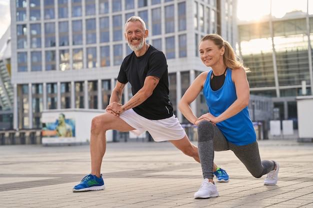 陽気なスポーティな中年カップルの男性と女性が一緒に走る準備をしてウォーミングアップ