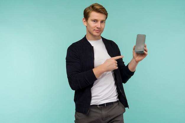 Веселый спортивный рыжий парень показывает пальцем на экране смартфона на синем пространстве.