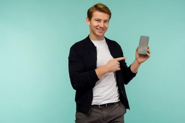 陽気なスポーティな赤い髪の男は、青いスペースのスマートフォンの画面に指を示しています。