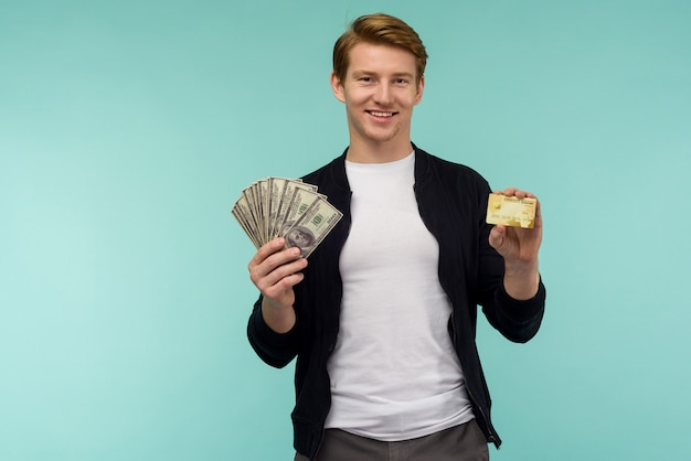 Cheerful sporty red-haired guy shows money and credit card on a blue background.