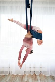 Веселая спортивная женщина в топе и леггинсах выполняет упражнения антигравитационной йоги в просторном оздоровительном клубе с панорамными окнами.