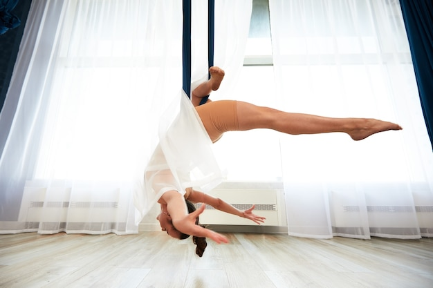 Веселая спортивная женщина в топе и леггинсах выполняет упражнения йоги антигравитации в просторном оздоровительном клубе.