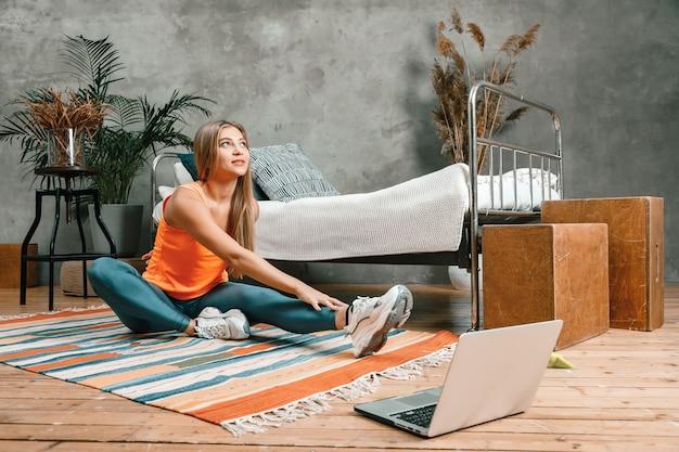 ブロンドの髪を持つ陽気なスポーティな女性が脚に伸びてラップトップで見ています