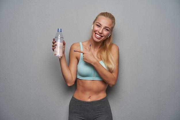 Allegra sportiva giovane donna bionda con i capelli lunghi tenendo la bottiglia d'acqua in mano e puntando su di essa con l'indice, guardando con gioia alla telecamera con un ampio sorriso, isolato su sfondo grigio chiaro