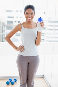 Cheerful sporty young woman holding flask
