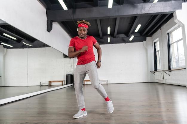 Веселый сильный мужчина с короткими дредами вдохновляется повторением танца