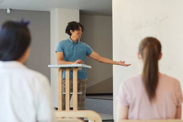 Cheerful student boy in casual outfit gesturing hand while presenting his research at university class