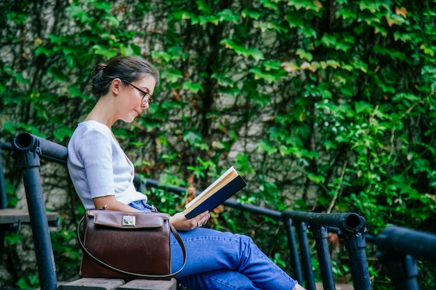 Cheerful student female with positive attitude reading a book