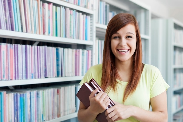 Cheerful student girl with books